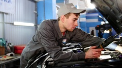 Mechanic in overalls looking to hood of the car - automobile service repairing Stock Footage