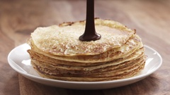 Slow motion of premium dark chocolate pour on freshly made blinis or crepes Stock Footage