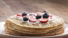 Slow motion of sprinkling sugar powder on blinis or crepes with fresh berries Stock Footage