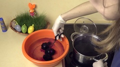 Hands take painted eggs from pot water with paint to plastic bowl with water Stock Footage