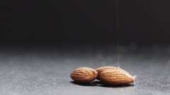 Slow motion of honey pouring over almond on slate board Stock Footage