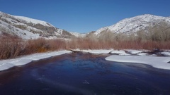 Aerial winter mountain valley snow ice river and pond 4K 028 Stock Footage