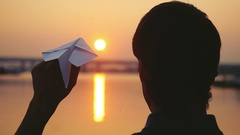 Young guy launch paper plane against the sea in slowmotion during sunset with Stock Footage