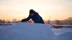 Kid playing in snowy mountains, to climb to the top. At sunset Stock Footage