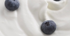 Blueberries in organic yogurt rotating loop video Stock Footage