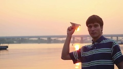 Young handsome man launch paper plane against the sea during amazing sunset with Stock Footage