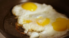 Cooking fried eggs with spice in frying pan for breakfast Stock Footage