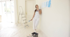 Young woman contemplating new paint for her home Stock Footage