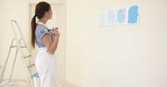 Young woman choosing a shade of blue paint Stock Footage