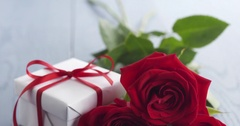 Three red roses with gift box on blue wood table pan Stock Footage