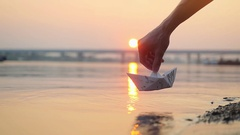 Man's hand putting paper boat on the water and pushing it away during beautiful Stock Footage
