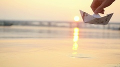 Man's hand launches paper boat on the water and pushing it away during beautiful Stock Footage