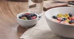 Pan over healthy breakfast cornflakes with berries poured with milk Stock Footage