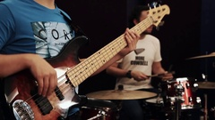 Young guys playing bass guitar and drum kit with purple curtain on background Stock Footage