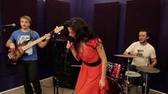 Songstress with fluttering hair singing into microphone with band, soundproofing Stock Footage