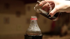 Woman's hand pours a drink back in the bottle like a Coke from a glass back Stock Footage