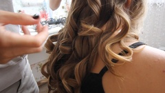 Hair stylist making curls on customer hair using electric curler Stock Footage