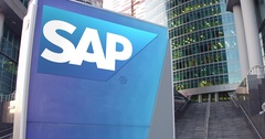 Street signage board with SAP SE logo. Modern office center skyscraper and Stock Footage