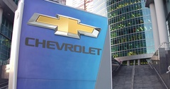 Street signage board with Chevrolet logo. Modern office center skyscraper and Stock Footage