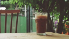 Girl puts a straw in the iced coffee Stock Footage