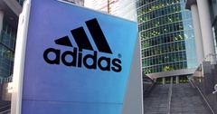 Street signage board with Adidas inscription and logo. Modern office center Stock Footage