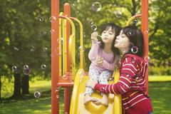 Mother and child blowing soap bubbles Stock Photos