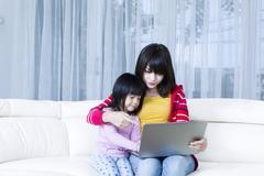 Mother and child with laptop on couch Stock Photos
