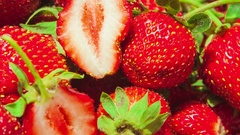 Macro of strawberries with two halfs in the center spinning in circles close up Stock Footage