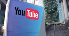 Street signage board with YouTube logo. Modern office center skyscraper and Stock Footage