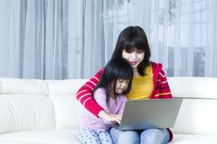Young mother and child playing laptop Stock Photos