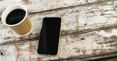 Disposable coffee cup and mobile phone on wooden plank Stock Footage