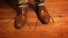 Man stands on floor with two untied shoes Stock Footage