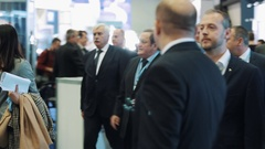 People walking along displays in hall of innavation business exhibition event Stock Footage