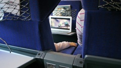 French kid traveling in fast train watching movie on laptop Stock Footage