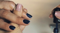 Woman manicurist hand putting dark blue magnetic nail polish in beauty shop Stock Footage
