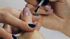 Female manicurist hand putting polish on golden blue nail in beauty shop Stock Footage