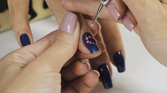 Woman manicurist hand putting white dots on blue nail polish in beauty shop Stock Footage