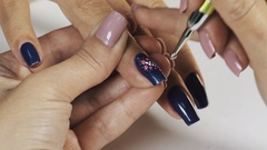 Female manicurist hand putting purple dots on blue nail polish in beauty shop Stock Footage