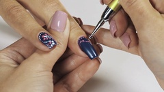 Female manicurist hand putting white dots on blue nail polish in cosmetic shop Stock Footage