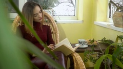 Beautiful young girl reading a book in a wicker rocking chair and looking out Stock Footage