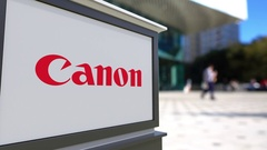 Street signage board with Canon Inc. logo. Blurred office center and walking Stock Footage