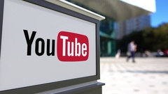 Street signage board with YouTube logo. Blurred office center and walking people Stock Footage
