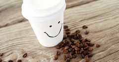 Smiley face on disposable cup with coffee beans on sack Stock Footage