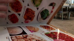 Motion of woman looking at menu turning pages Stock Footage