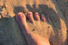 Bare foot covered with sand Kuvituskuvat