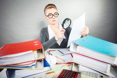 Businesswoman explore documents with big loupe. Stock Photos