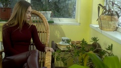 Beautiful young stylish girl sits in a wicker chair drinks hot aroma coffee and Stock Footage