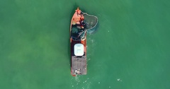 Aerial: Fishermen working on a sailboat take out a network of sea. Stock Footage