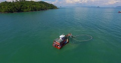 Aerial: Fishermen working on a fishing boat, lifted out of the sea fishing net. Stock Footage