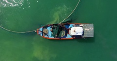 Aerial: Fishermen on a boat take out a network of sea. Stock Footage